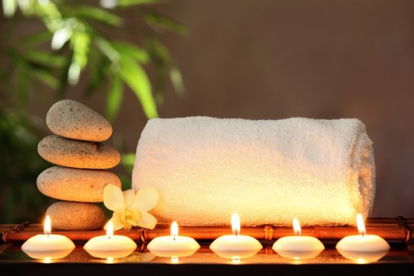 Six little candles in fornt of a white towel and four rocks placed one on another