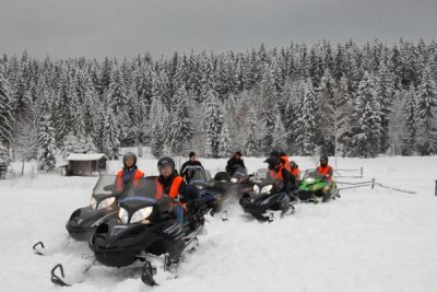 People riding on snowmobiles during winter near Złoty Groń Hotel