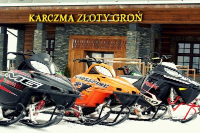 One orange and two black snowmobiles in fornt of entrance to hotel s inn